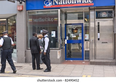 LONDON, UK - AUGUST 9: London Riots. Unidentified members of the public and police outside a branch of Nationwide damaged in the riots. August 9, 2011 in London UK.