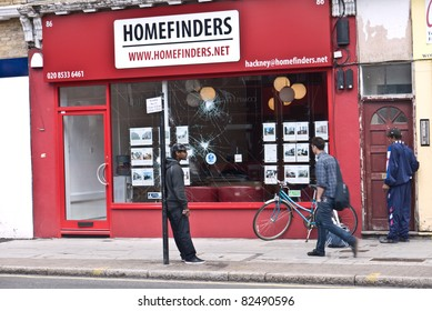 LONDON, UK - AUGUST 9: London Riots.Unidentified men outside Homefinders office where windows have been smashed in the riots along Amhurst road Hackney. August 9, 2011 in London UK.