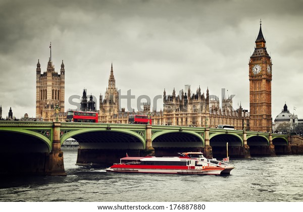 London, the UK. Big Ben, the Palace of Westminster and the River Thames. Red buses, red boat, the icons of England in vintage, retro style