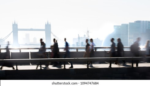 London, UK. Blurred image of office workers crossing the London bridge in early morning on the way to the City of London. Tower bridge at the background