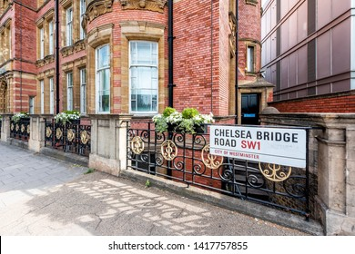 London, UK Chelsea Embankment green plants flowers in summer with street Bridge sign by historic brick building