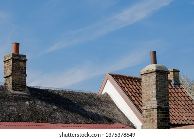 London, UK - Circa April 2019: Detailed view of brick-buit chimneys seen atop a very old cottage during midday. Both thatched and tiles can be seen on the roof construction which is an usual feature.