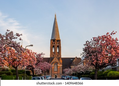 London U.K. Circa April 2019 the famous st Jude's Church designed by Edwin Lutyens sits high above North Square in Hampstead Garden Suburb.Beautiful blossom trees adorn the streets leading up the hill