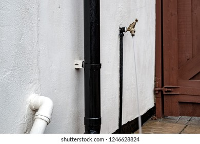 London, UK - Circa December 2018: Isolated view of a running outside brass tap. Taken using a slow shutter the water forms a blur against the outside wall. Used for garden irrigation.
