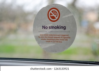 London, UK - Circa December 2018: Shallow focus of a hotel No Smoking Sticker seen within a room's window. Cars can be seen in the distant next to a bust road junction in central London.