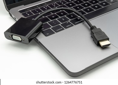 London, UK - Circa December 2018: Detailed image of a HDMI video adapter seen laying on the keyboard of an opened, well-known brand of Notebook computer. Used for connection to an external display.