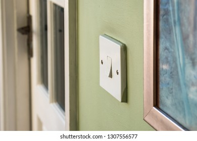 London, UK - Circa February 2019: Isolated image of an interior light switch in the off position. Seen next to a small wall painting and an interior wooden door leading to a utility room.