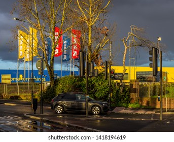 London U.K. Circa February 2019 A dramatic storm of rain and thunder creates an eerie urban landscape in Neasden NW London.The red and yellow IKEA flags flutter in the dark sky background.