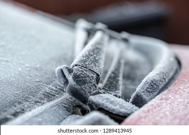 London, UK - Circa January 2019: Shallow focus view of ice crystals formed on part of a car's windshield wiper blade assembly during winter. The windshield is heavily frosted and will be defrosted.