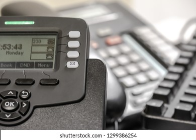 London, UK - Circa January 2019: Shallow focus image of a generic VOIP business telephone showing part of its keypad and LCD display. Located on a business desk with out of focus phones in the distant