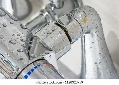 London, UK - Circa July 2018: Close-up, shallow focus of a modern metal shower and bath hot and cold water control valve. Shown with droplets of water and condensation after a shower.