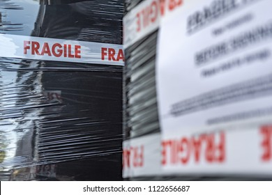 London, UK - Circa June 2018: Close-up, shallow focus of fragile warning tape seen attached to black shrink wrap on fragile goods in an outdoor dispatch area. The black wrap is used for waterproofing