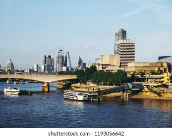 LONDON, UK - CIRCA JUNE 2018: Waterloo bridge, the National Theatre and river Thames view at sunset, with the city skyscrapers in the background