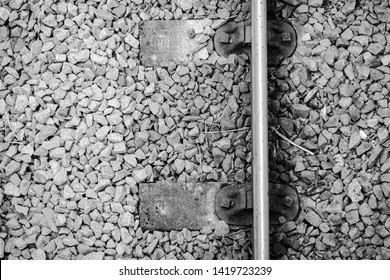 London, UK - Circa June 2019: Abstract view of newly installed steel railway track seen attached to a pair of railway sleepers. Stone ballast can be seen in the background on which the track is laid.
