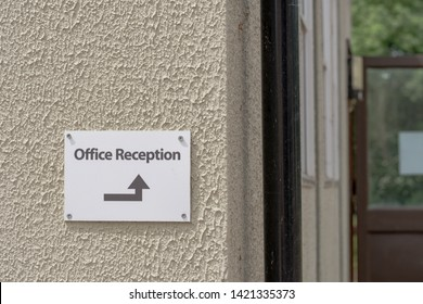 London, UK - Circa June 2019: Shallow focus of a newly installed Office reception direction sign attached to the outer wall of a temporary office unit. The distance shows the office door opened.