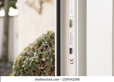 London, UK - Circa March 2019: Shallow focus of CE marking and other conformances on newly installed uPVC double glazed door. Details of the rubber seal is seen. A shrub by the back door is seen.