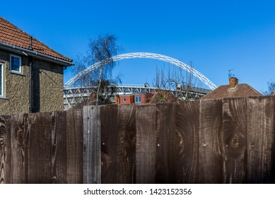 London U.K. Circa March 2019 Wembley stadium arch can bee seen from many vantage points in and around London.This viewpoint shows its urban setting amongst the Suburban houses and gardens of the area