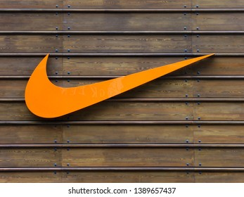 LONDON, UK - CIRCA MAY 2012: Orange Nike logo on a wooden wall at the official Nike store at Westfield Stratford City shopping centre.