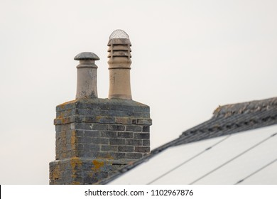 London, UK - Circa May 2018: Isolated view of a newly install Solar Panel on a house roof, in contrast to a very old Chimney used for wood burnin, one giving no emissions, the other creating pollutant