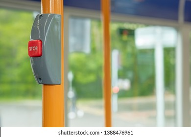 London, UK - Circa May 2019: Shallow focus of a red stop button seen inside a public bus. Used to request the driver to stop at a forthcoming bus stop. Seen with yellow handrails during a busy commute