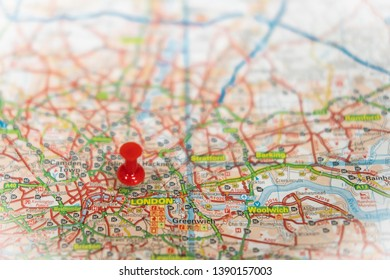 London, UK - Circa May 2019: Shallow focus of a red push pin located in the centre of the English capital. The map shows the large road network in the capital and the River Thames in the east.