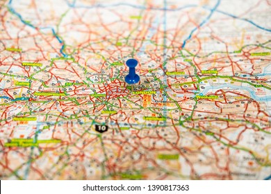London, UK - Circa May 2019: Shallow focus view of a blue push pin seen located in the heart of England's capital city. Details of the extensive road network can be seen as is the River Thames.