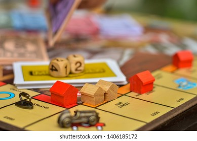 London, UK - Circa May 2019 Metal car game piece with dice and wooden red house pieces with cards in the background placed on free parking sign on Monopoly board game