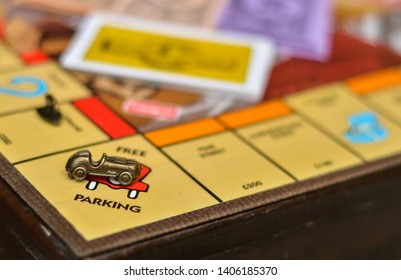 London, UK - Circa May 2019 Metal car game piece with cards in the background placed on free parking sign on Monopoly board game
