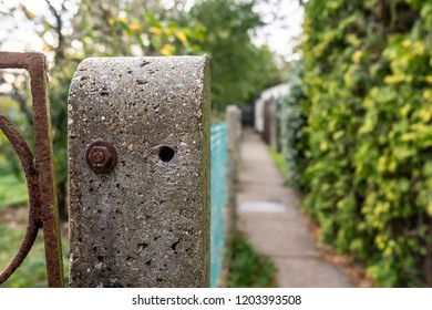 London, UK - Circa October 2018: Close-up, shallow focus view of a concrete fence post showing a rusty bolt used to help hold up the wire fencing. Part of a rusty gate can also be seen on the left.