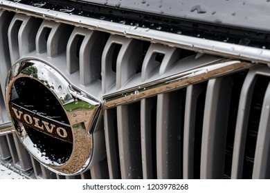London, UK - Circa October 2018: Close-up, shallow focus of a well known logo at the front of a Swedish built SUV hybrid SUV. Should after a downpour, water can be seen on the bonnet and grille area