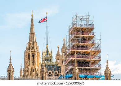 London, UK closeup view of Big Ben clock bell tower construction scaffold scaffolding metal frame in city and Westminster Palace with flag