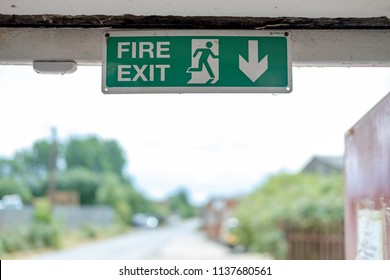 London, UK - Crica July 2018: Shallow focus, isolated image of a green Fire Exit sign seen attached an internal factory door frame, leading to the outside of the factory for fire emergencies.