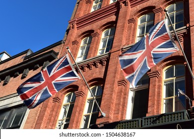 London, UK, dated 1st Sept 2019. Picture of british flags, union jack flying in the wind on a traditional facade made of red bricks.