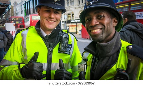 LONDON, UK - DEC 12, 2015: Two London policemen on foot patrol in Oxford Street in the heart of London.