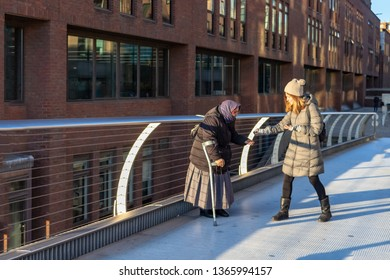LONDON, UK – Dec 13, 2018: Old beggar receiving money from a kind young woman