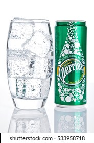 LONDON, UK - DECEMBER 06, 2016: Glass with ice and tin of Perrier sparkling water. Perrier is a French brand of natural bottled mineral water sold worldwide.