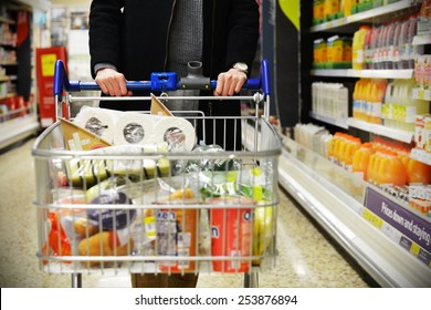 London, UK - December 12, 2014: A shopper browses an aisle of a Tesco supermarket store. Britain's Tesco is the world's third largest supermarket chain after America's Walmart and France's Carrefour.