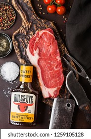 LONDON, UK - DECEMBER 13, 2018: Bottle of Bull's Eye Tennessee style sweet whiskey sauce with raw sirloin beef steak on vintage chopping board with knife and fork on rusty board
