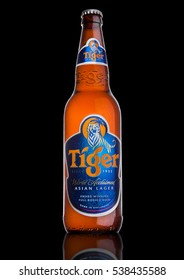 LONDON, UK, DECEMBER 15, 2016: Bottle of Tiger Beer on black background, First launched in 1932 is Singapore's first brewed beer.