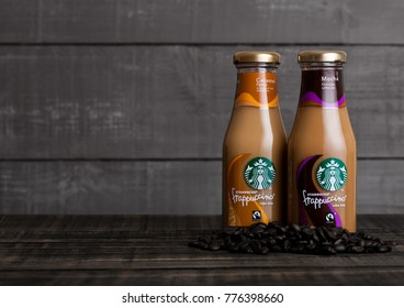 LONDON, UK -DECEMBER 15, 2017: Glass bottles of Starbucks frappuccino coffee drink with caramel on wooden background. Seattle based Starbucks is the largest coffeehouse company in the world.