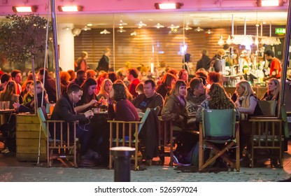 London, UK - December 19, 2015:  People in the restaurant, well lit up outside patio