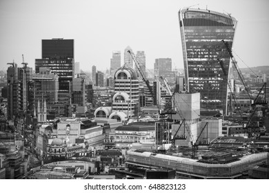 London, UK - December 19, 2016: City of London business area view at sunset. View includes Walkie-Talkie building and Canary Wharf business district at the background
