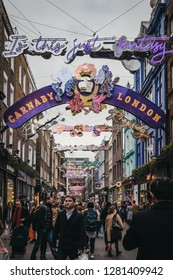 London, UK - December 19, 2018: People walking under Bohemian Rhapsody themed Christmas lights in Carnaby Street, pedestrianised shopping street in Soho with over 100 shops and restaurants.