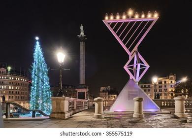 LONDON, UK - DECEMBER 19: Night shot of Menorah next to Christmas tree in Trafalgar Square, set up for Chanukah. December 19, 2015 in London.