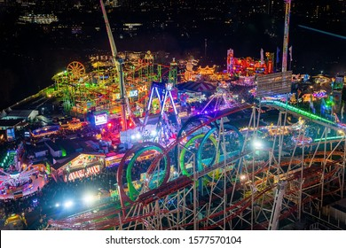 London, UK. December 2, 2019. London Wonderland. Night view of people walking in the Hyde Park's winter Wonder Land between different rides and attractions. Beautiful Christmas spirit in London.