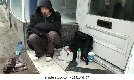London, UK December 2018: Homeless man sitting in doorway begging at Christmas in the rain with a few coins on a plastic bag.