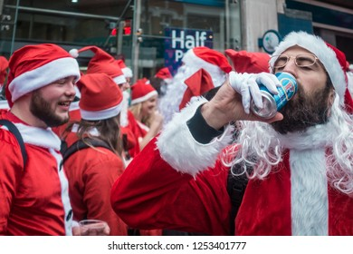 London, UK - December 2018 : Man dressed in santa outfit drinking alcoholic beer from a can while taking part in a themed SantaCon event
