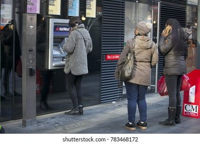 London, UK - December 22, 2017: People stand in line to the ATM to withdraw money near Liverpool street