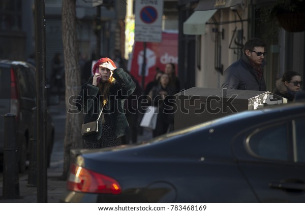 London, UK - December 22, 2017: Area near Liverpool street at noon in the backlight. A girl is talking on the phone, covering her eyes with her hand from the sun