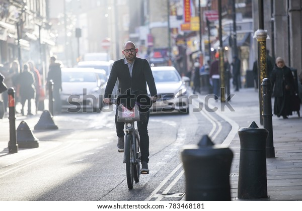 London, UK - December 22, 2017: Street Brick lane at noon in the backlight. People hurry about their business. A man riding a bicycle on the road. East London